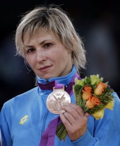Bronze medalist Guzel Manyurova of Kazakhstan shows her medal after the victory ceremony for the 72-kg women's freestyle wrestling competition at the 2012 Summer Olympics, Thursday, Aug. 9, 2012, in London. (AP Photo/Paul Sancya)